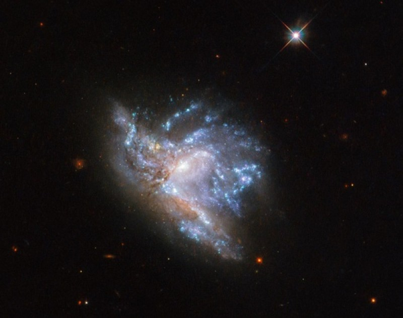 Hubble spies a dazzling collision between two galaxies in Hercules